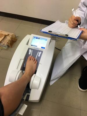 踵(かかと)で骨密度を測定中…